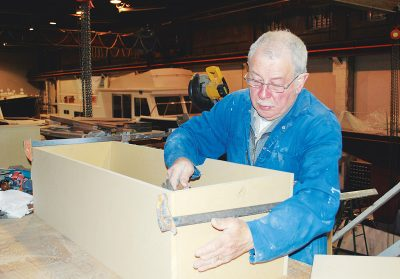 Longtime employee John Silveira assembles a cabinet for the Abaco 40 in the mezzanine workshop.